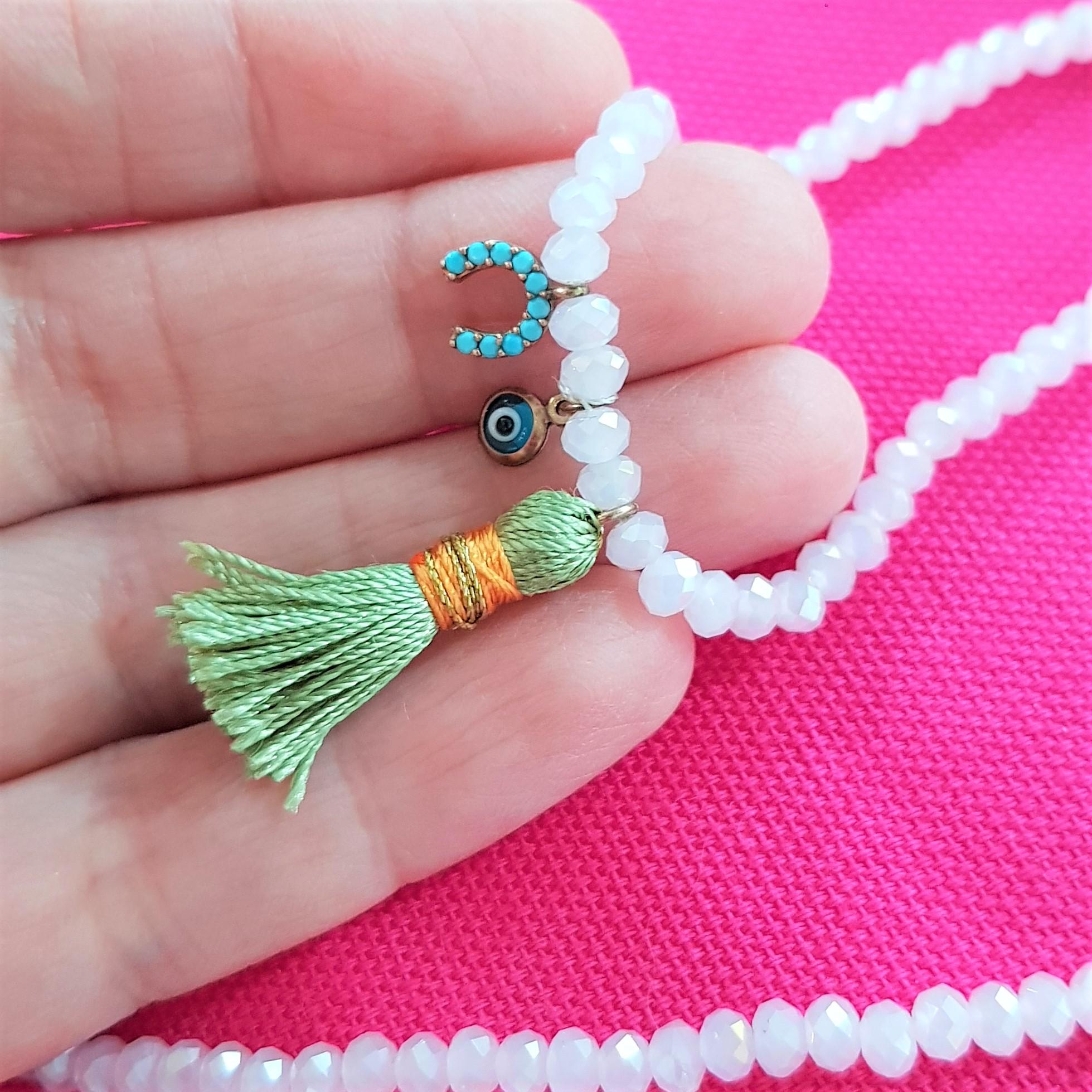 closeup pink tassel & charm bracelet